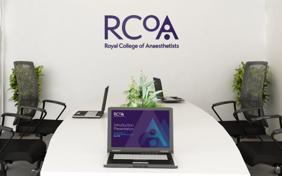 Meeting room with RCoA logo on the back wall and a laptop displaying branding presentation.