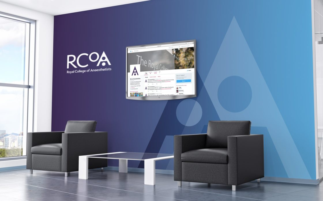 Waiting area with arm chairs and coffee table infant of a two tone wall (purple and blue) with the RCoA logo and TV displaying the Twitter page.