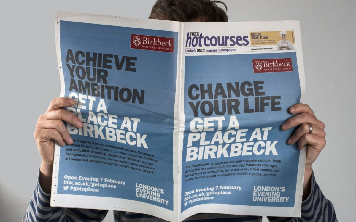 Man holding up newspaper in front of his face with Birbeck advertisement on from and back.