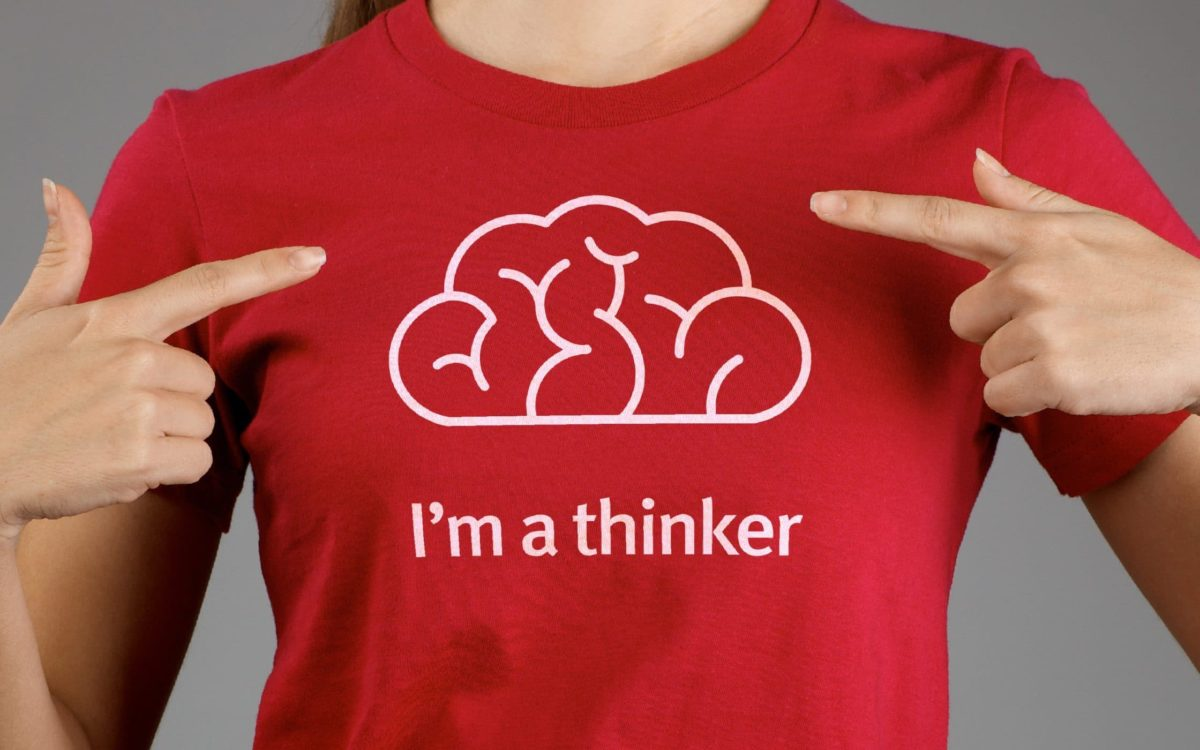 """Close-up of lady pointing to her red T-shirt with brain imagery accompanied by text which reads """"I'm a thinker""""."""