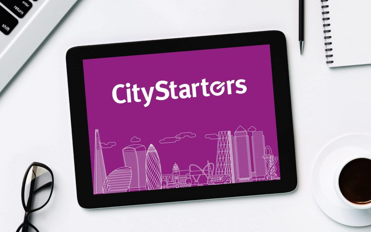 Tablet with the CityStarters logo above London's skyline surrounded by accessories.