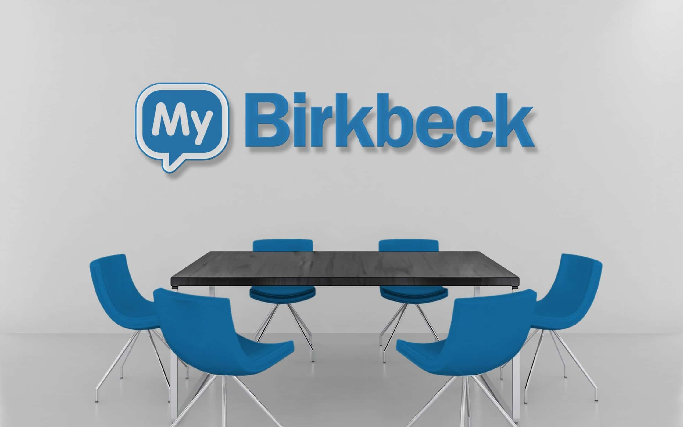 My Birkbeck logo on a wall behind table and chairs.