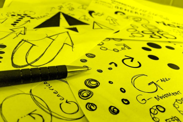 Pen over several spread sheets of paper with doodles on.