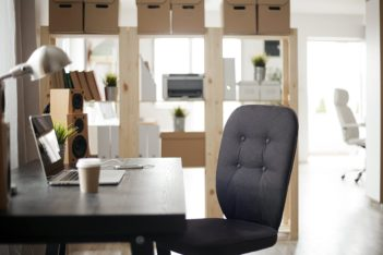 Photo of a home office with desk which has a laptop, speakers, phone and coffee in foreground.